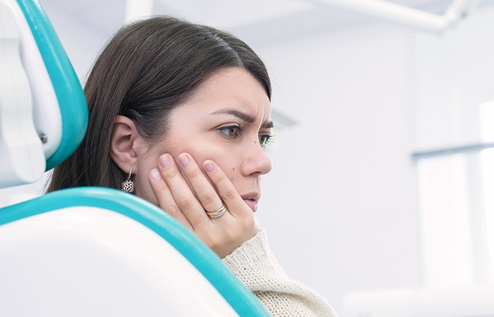 Woman holding cheek in dental chair