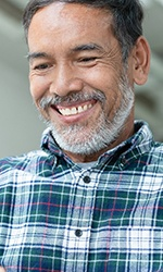 An older man wearing a plaid shirt and holding a smartphone smiling while inquiring about dental implants