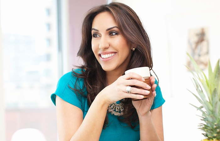 Woman smiling holding coffee cup
